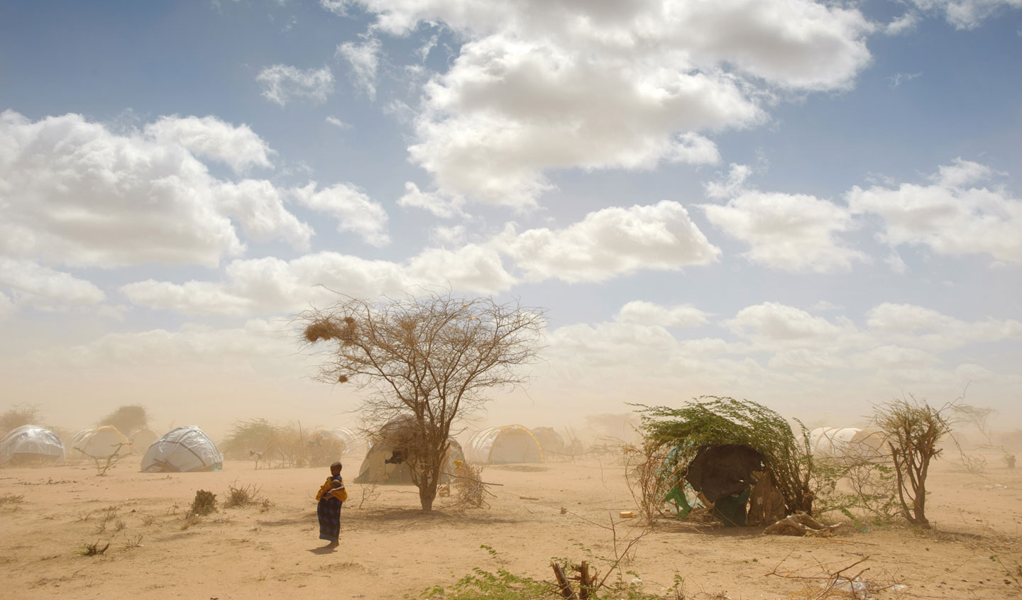 In Dabaad, a dusty refugee camp in Kenya, an African woman stands surrounded by makeshift shelters.