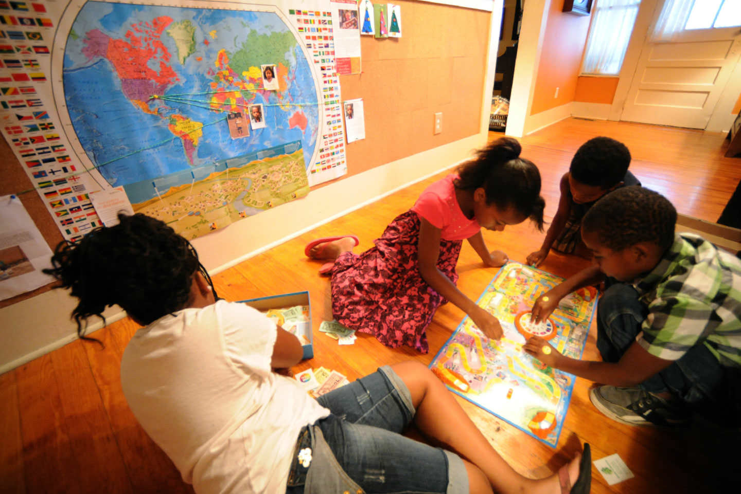 Simone Thomas, Fantazia Savage, Jayden Thomas, and Derrick Wilder play below a Brown House map marking the places their sponsored children live.