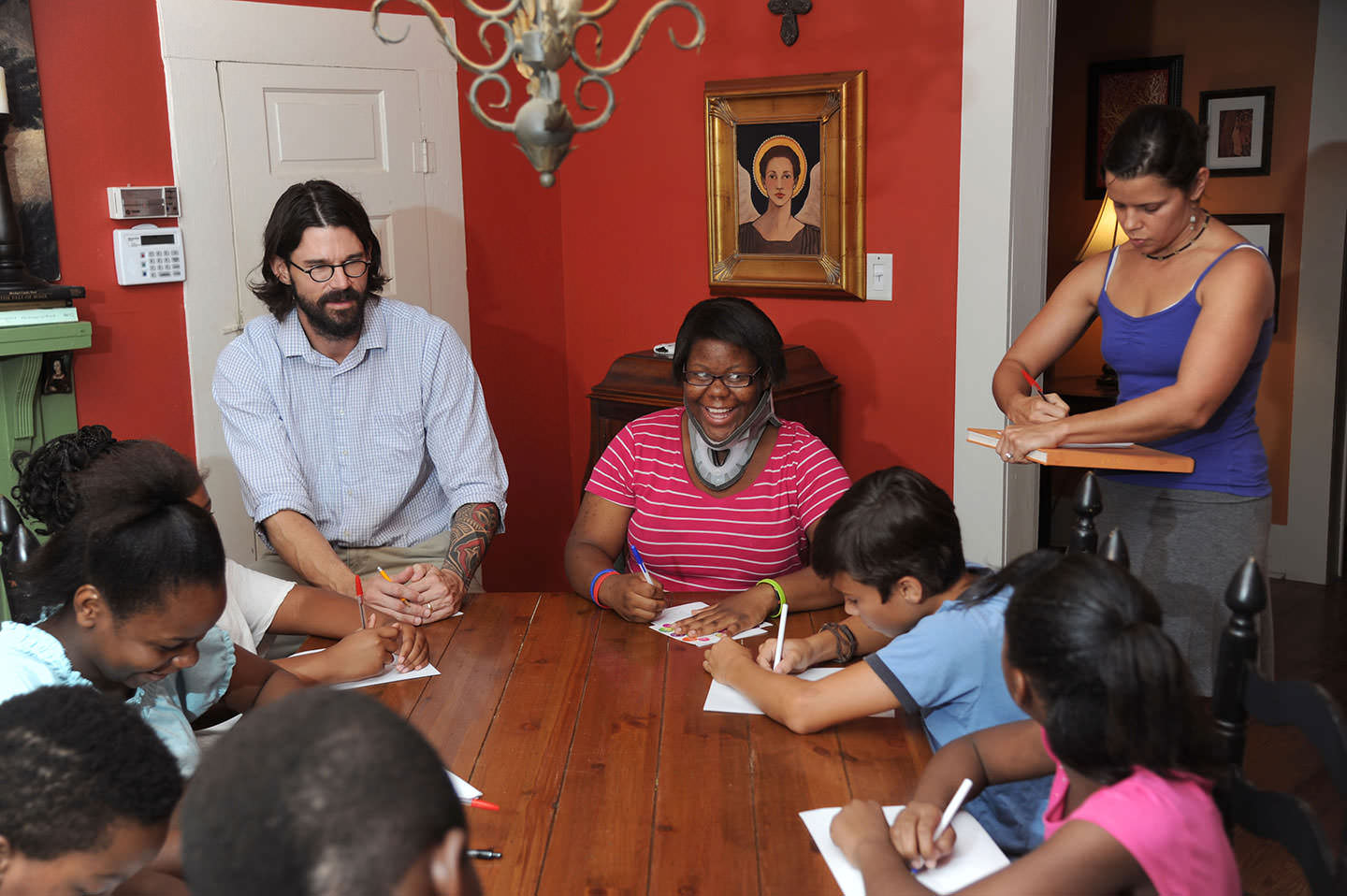Adam Pierce, left, and Amy Pierce, far right, work with the kids from West Circle at the Brown House.