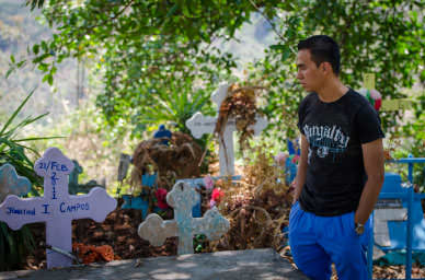 Daniel visits the grave of his friend who was killed recently; most community members believe his death is due to gangs.