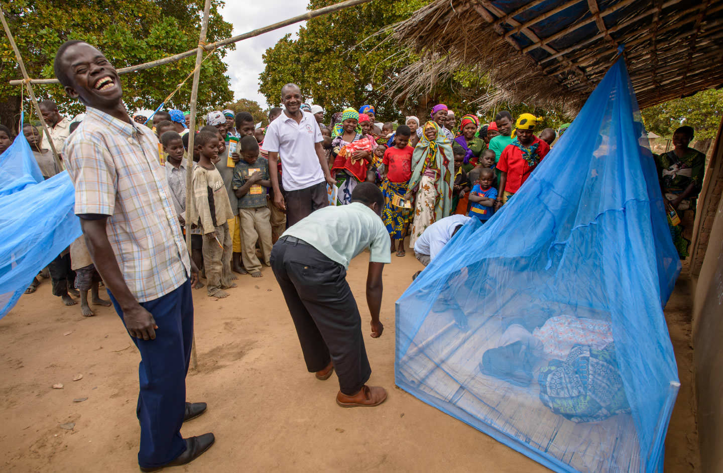 World Vision staff teach a nearby community to use nets properly.